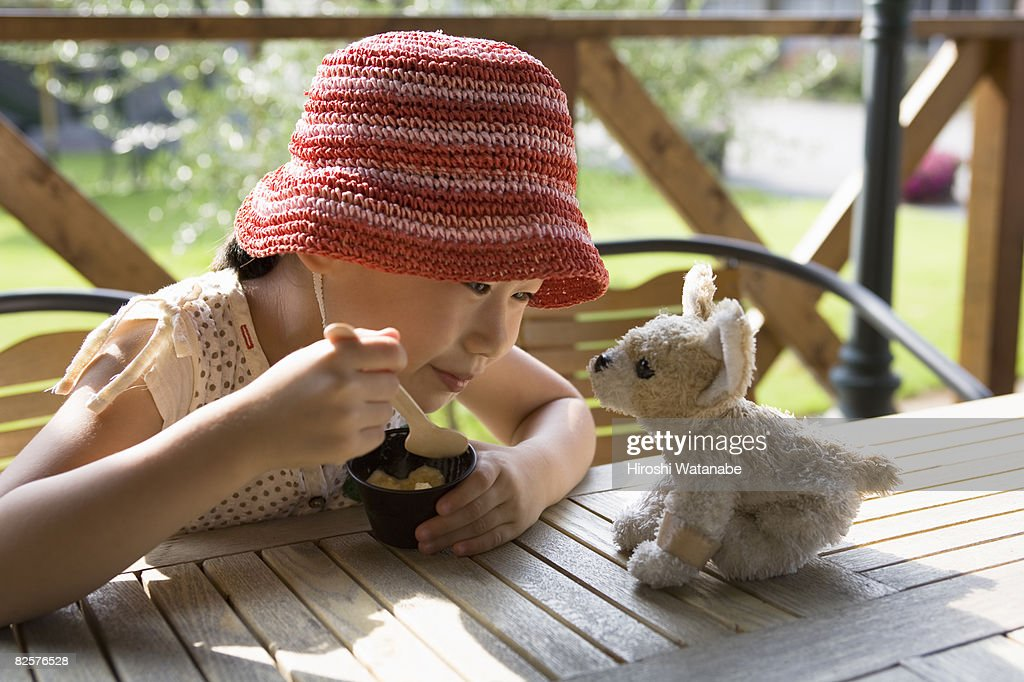 Girl eating ice cream, looking at a toy dog : Stock Photo