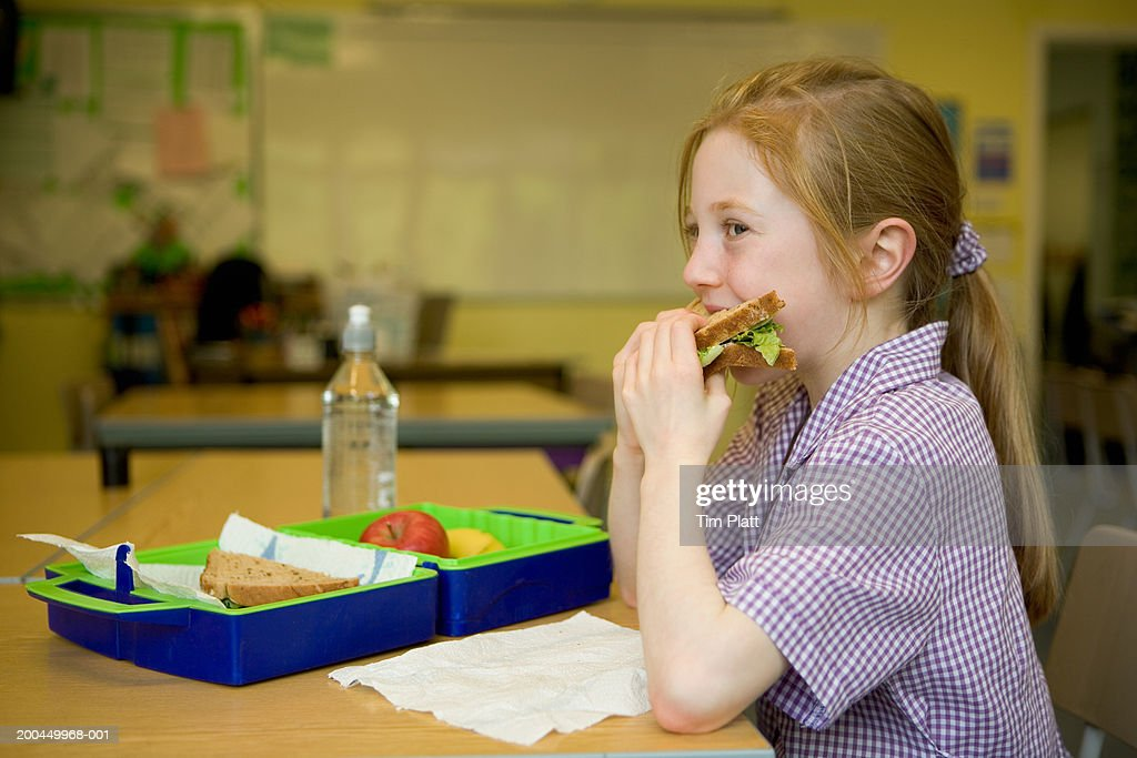 Girl (7-9) eating lunch in school lunchroom, side view : Stock Photo