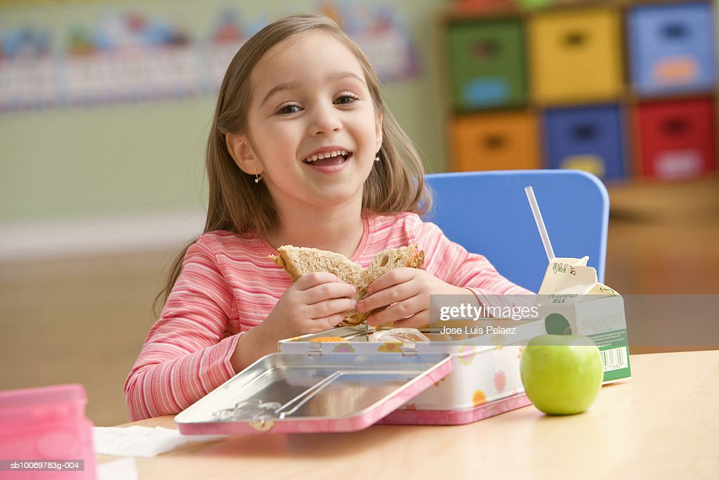 Girl (4-5) eating lunch, smiling, portrait : Stock Photo