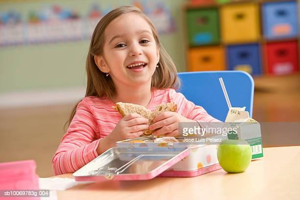 Girl (4-5) eating lunch, smiling, portrait