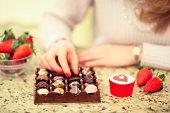 Girl Eating Luxury Chocolates and Strawberries