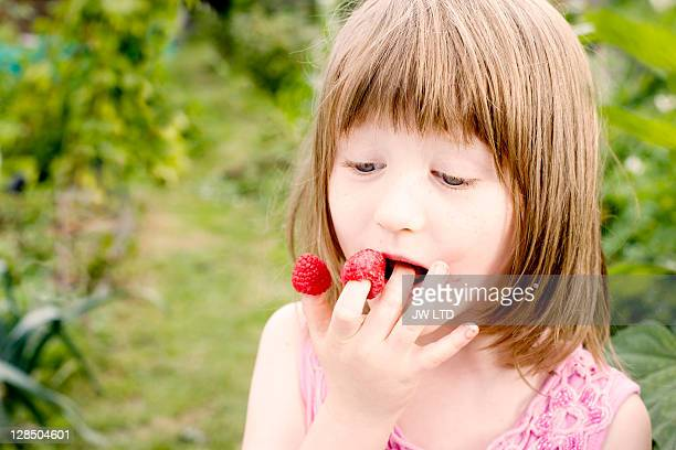 Girl eating raspberries off fingers, close up