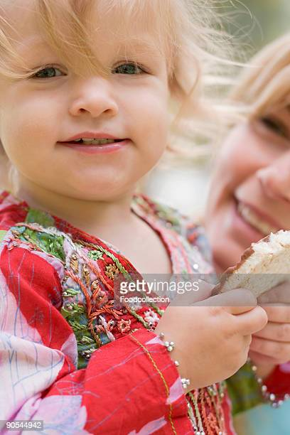 Girl (2-3) eating rice cake, woman in background