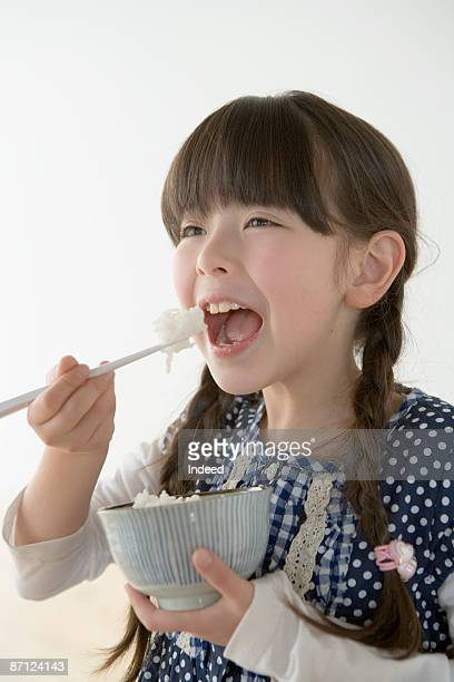 Girl (8-9) eating rice with chopsticks