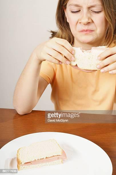 Girl eating sandwich, making face