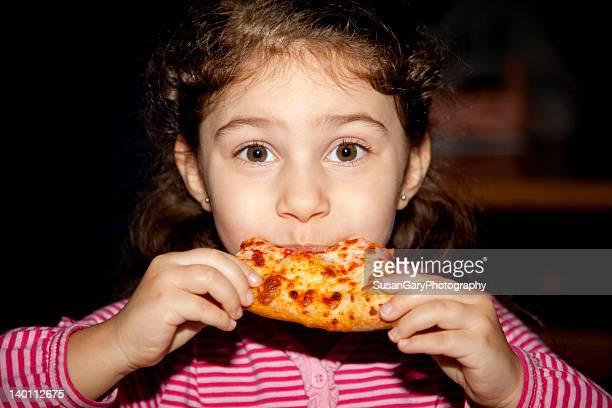 Girl eating slice of pizza