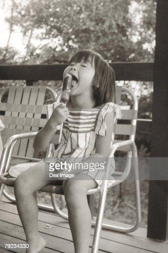 Girl eating snack at balcony : Stock Photo