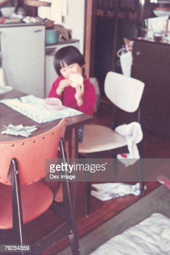 Girl eating snack at kitchen : Stock Photo