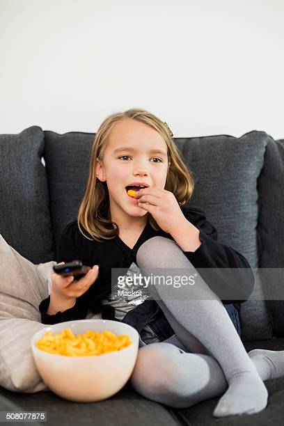 Girl eating snacks while watching TV on sofa at home