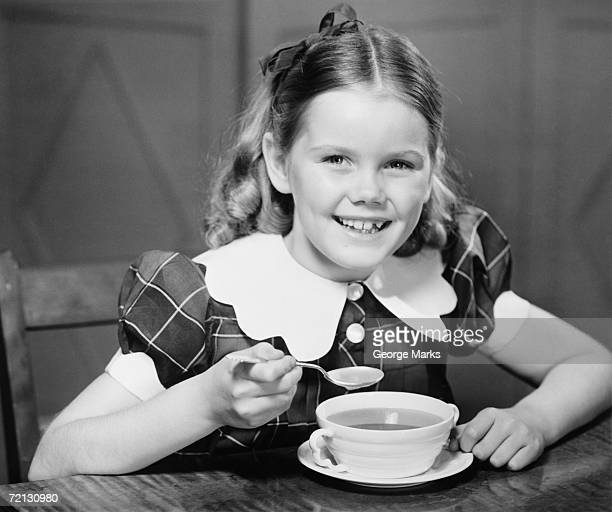 Girl (10-11) eating soup at table (B&W), portrait