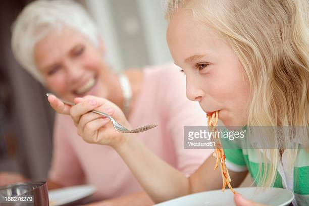 Girl (10-11) eating spaghetti, grandmother in background