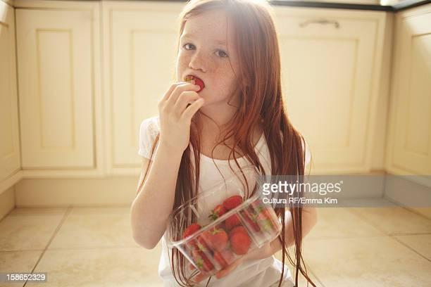 Girl eating strawberry on kitchen floor