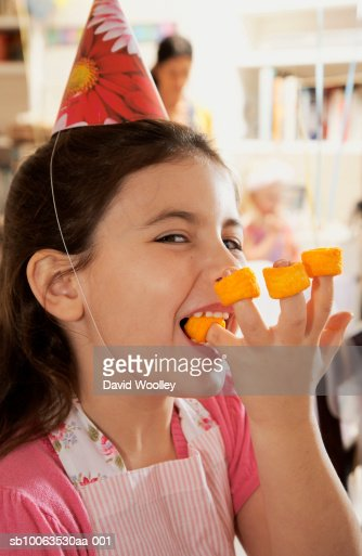 Girl (6-7) eating tubular crisps, portrait, close-up : Stock Photo