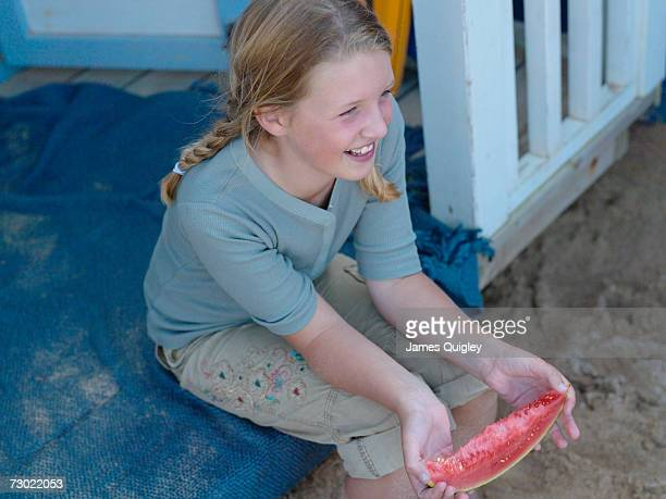 'Girl (8-10) eating watermelon on porch, high angle view'