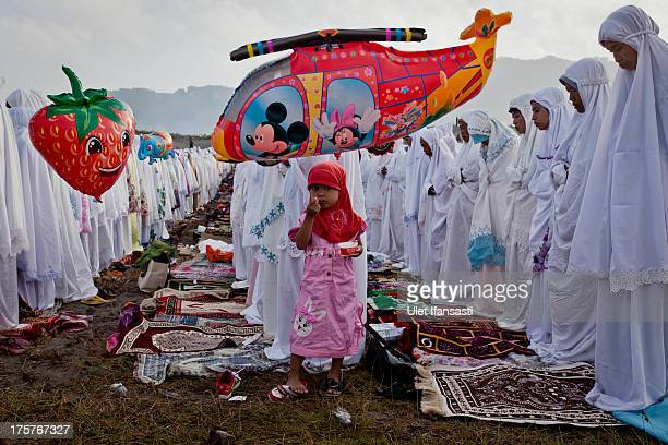 A girl eats ice cream as Indonesian muslims perform Eid AlFitr prayer on 'sea of sands' at Parangkusumo beach on August 8 2013 in Yogyakarta...