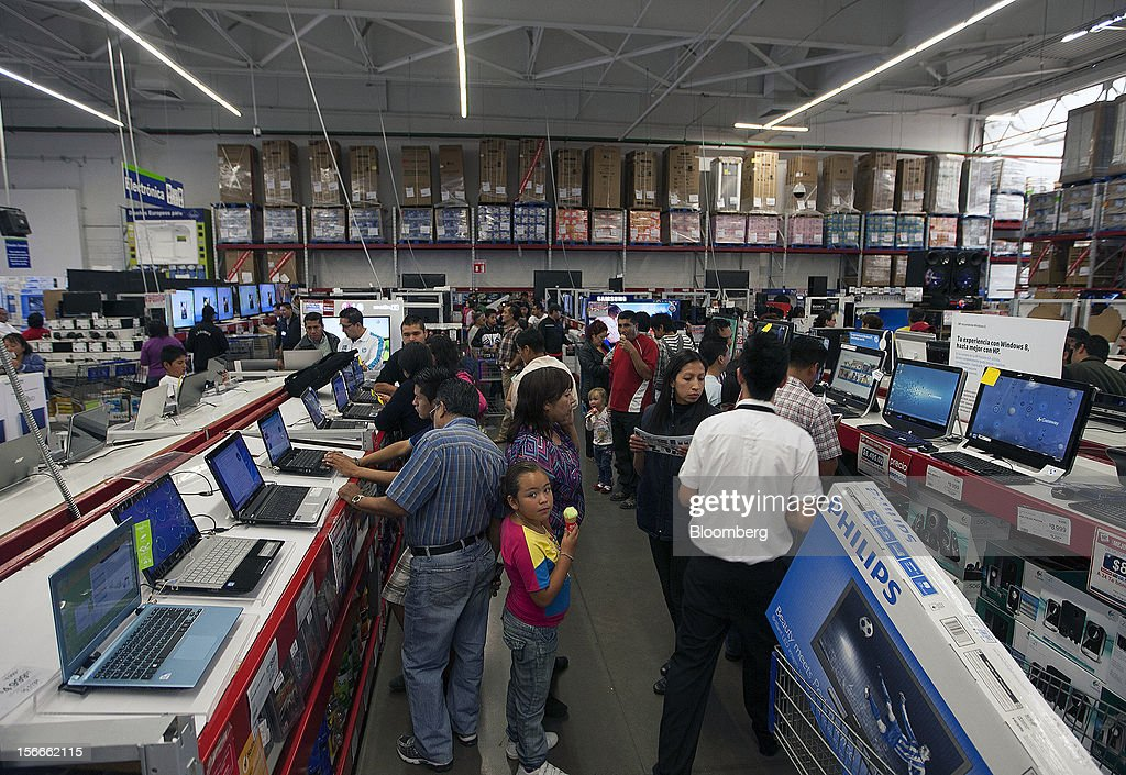 A girl eats ice cream while shoppers look at laptop computers in the electronics department inside a Sam's Club store in Mexico City, Mexico on Saturday, Nov. 17, 2012. El Buen Fin, Mexico's equivalent of Black Friday, when the year's biggest discounts are offered by participating stores, is held on the third weekend of November and will run through Nov. 19. Photographer: Susana Gonzalez/Bloomberg via Getty Images