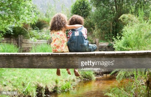 Girl embracing boy on footbridge over stream : Stock-Foto