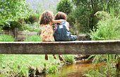 Girl embracing boy on footbridge over stream