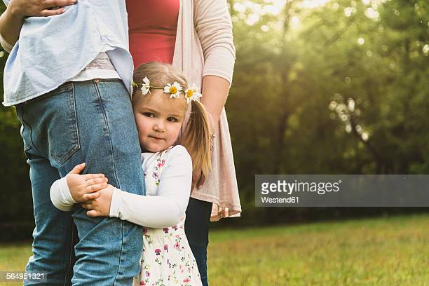 Girl embracing fathers leg on meadow