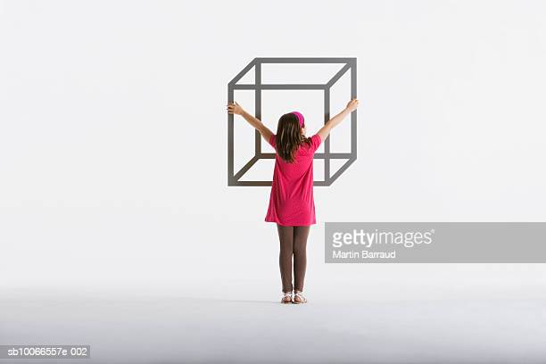 Girl (8-9) embracing geometric outline of box on white background, rear view