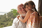 Girl (4-6) embracing grandfather, smiling, portrait of man, close-up