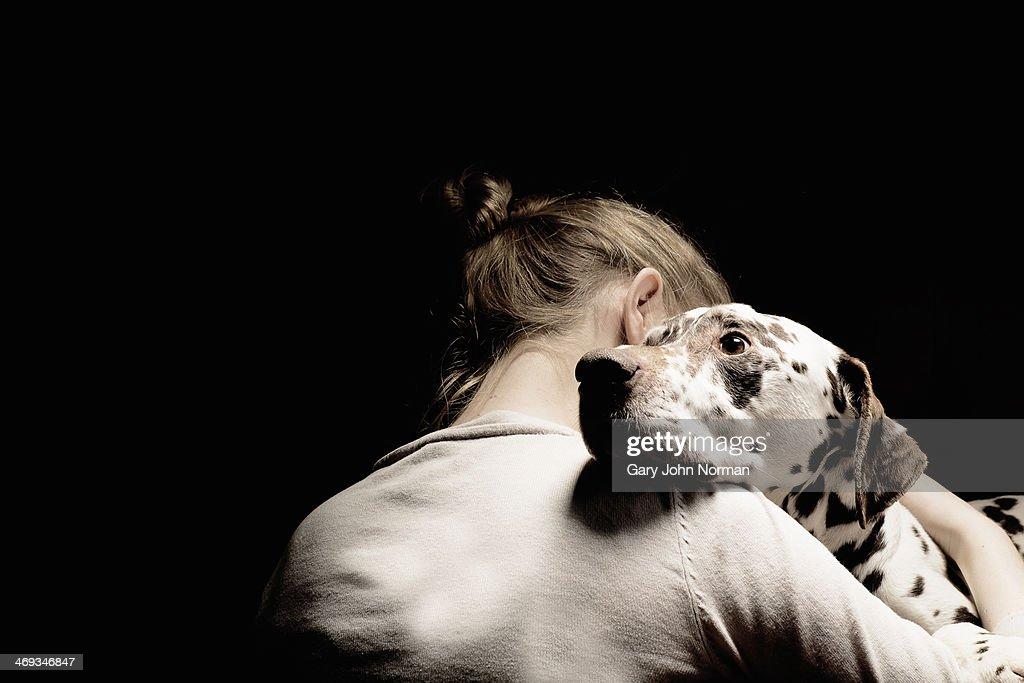 girl embracing her dog, studio shot : Stock Photo