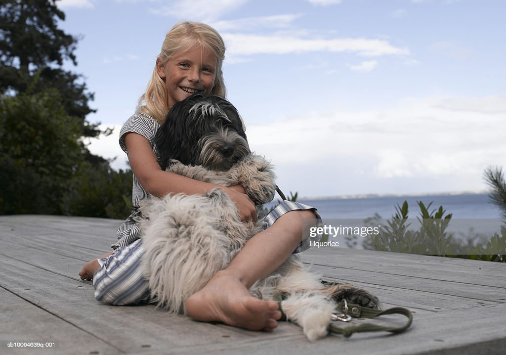 Girl (8-9) embracing poodle on pier, smiling, portrait : Stock Photo