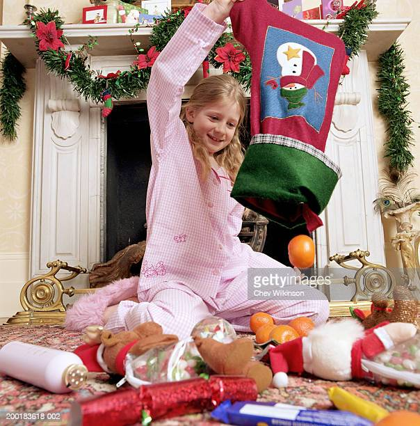Girl (7-9) emptying Christmas stocking onto floor, smiling