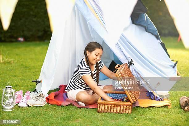 Girl emptying picnic basket in front of homemade tent in garden