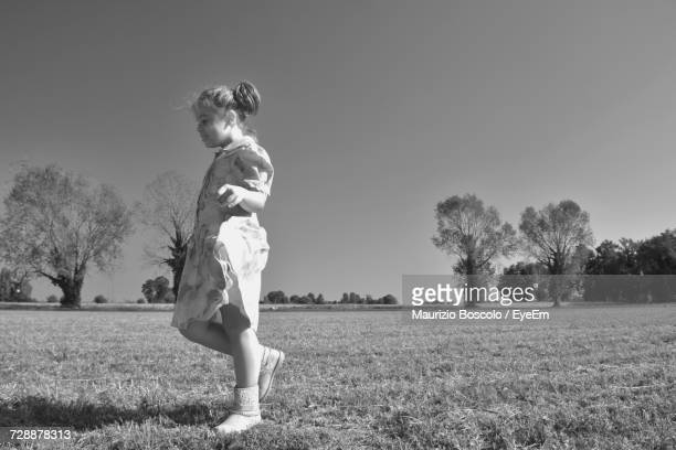Girl Enjoying On Grassy Field Against Clear Sky
