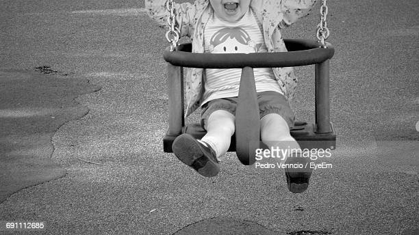 Girl Enjoying On Swing At Park