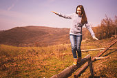Girl enjoying the nature walking on the balance beam