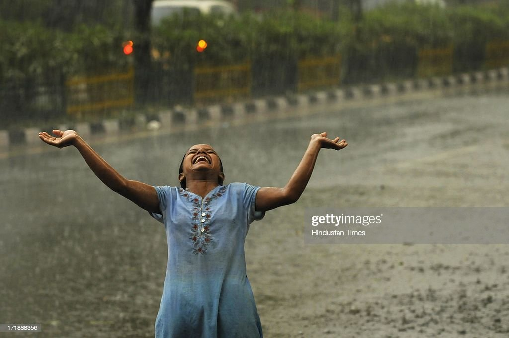 A girl enjoys during a heavy rainfall after a hot and humid afternoon on June 29, 2013 in Noida, India. Weather department forecast the country will receive normal rains this year, raising prospects of a stronger performance by Asia's third-largest economy.