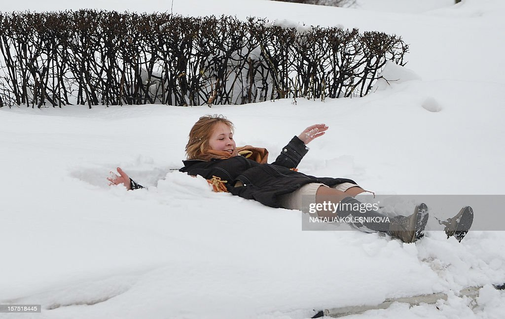 A girl enjoys snow in central Moscow, on December 4, 2012. Muscovites woke up today to a thick blanket of snow covering the Russian capital.The temperatures in Moscow reached today 1C (34 F), but due to high humidity and wind, weather experts said it would feel more like - 3C (25 F).