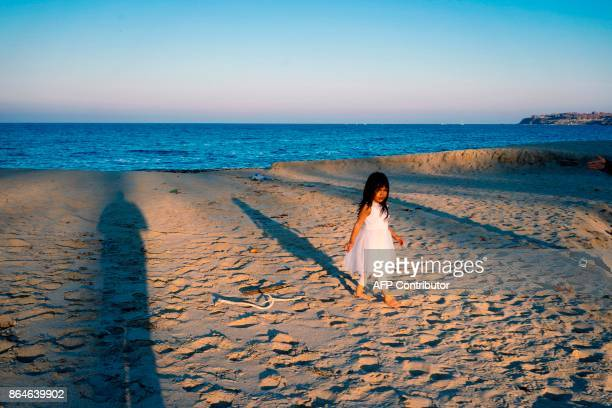 girl enjoys the warm autumn weather on a beach near the Black sea town of Sozopol on October 21 2017 / AFP PHOTO / Dimitar DILKOFF