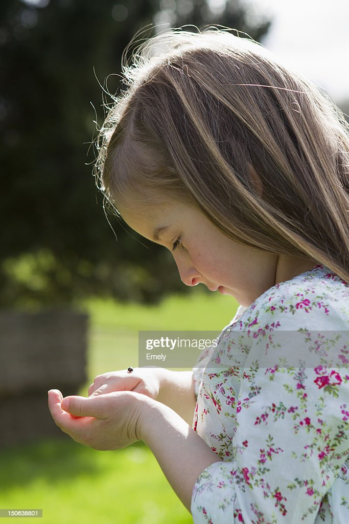 Girl examining insect on hand outdoors : Stock Photo