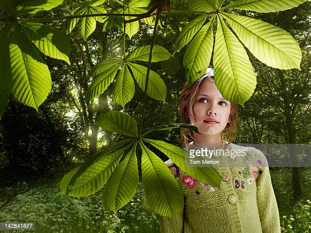 Girl examining leaves in forest