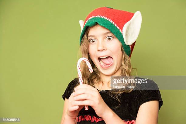 Girl excited to eat a candy cane.