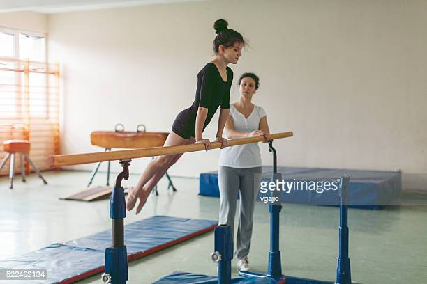 Girl Exercise On Gymnastics Bar.