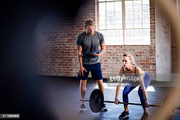 Girl exercising with weights headed by her personal trainer