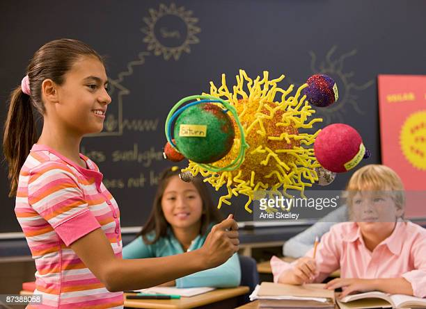 Girl explaining solar system to classmates