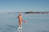 Girl extreme sportswear in a swimsuit on the ice. Ice lady. A female beginner skater skates and poses on skates, and tans. She has a beautiful body, strong health and great courage. It's freezing outs