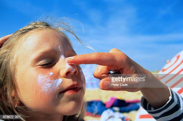 Girl (4-6),eyes closed,having sun block applied to cheeks and nose
