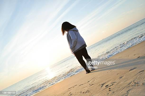 Girl facing Atlantic Ocean at sunrise