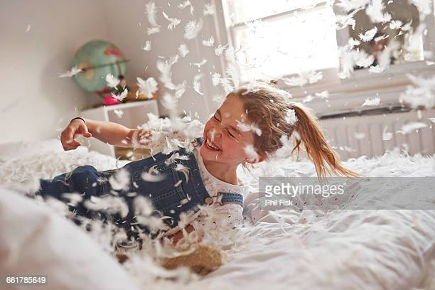 Girl falling on feather pillow fight bed