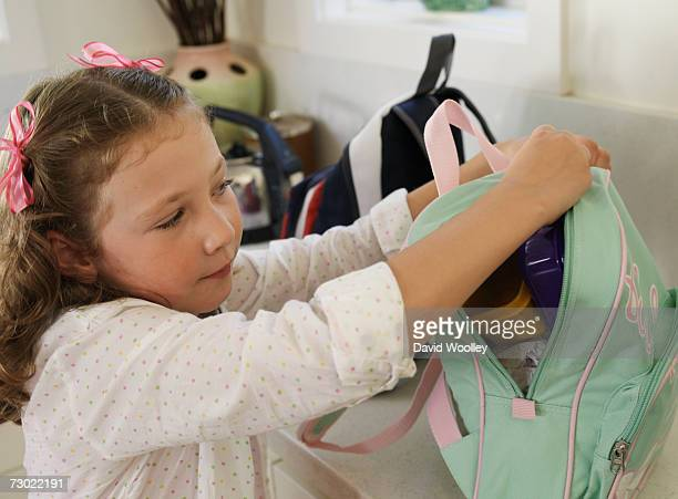 'Girl (6-7) fastening backpack in kitchen, elevated view'