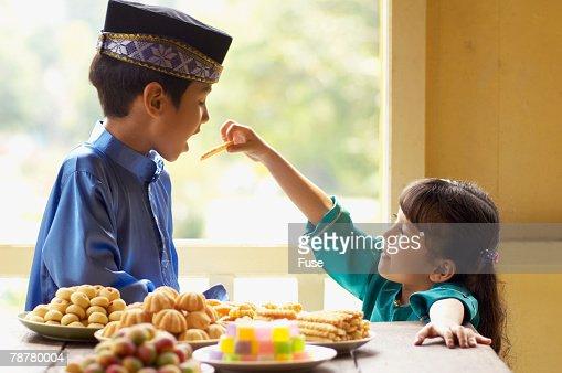 Girl Feeding Boy Sweets for Malaysian New Year