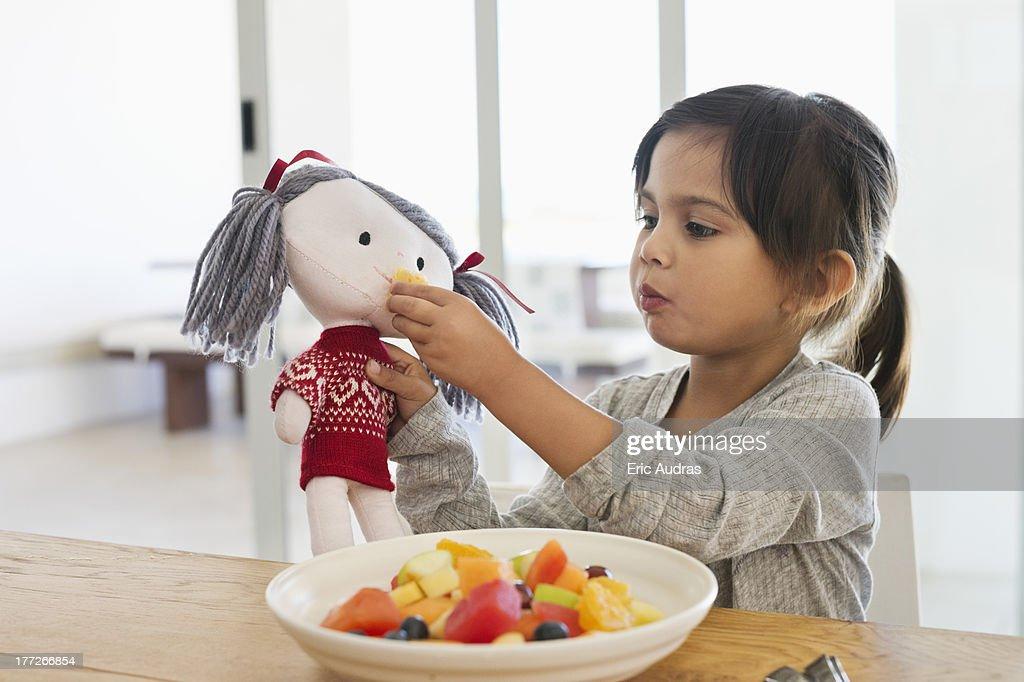 Girl feeding fruit salad to her doll