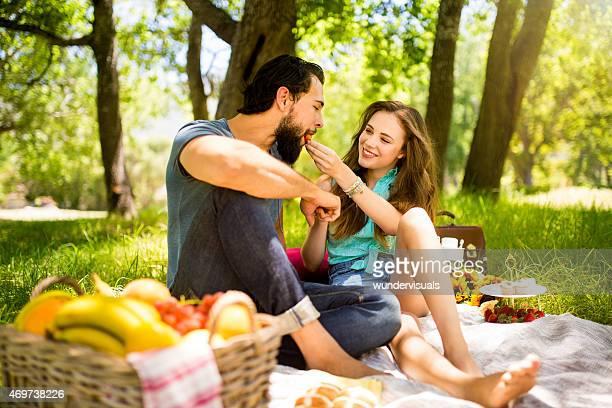 Girl feeding her boyfriend a strawberry at a picnic