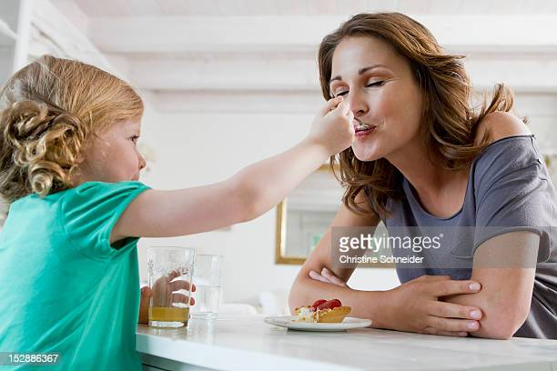 Girl feeding mother breakfast
